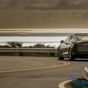 Tesla rijdt tijdens zonsondergang in een bocht.