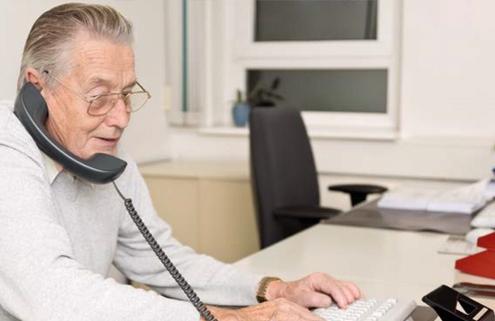 senior zit aan de telefoon achter een computer