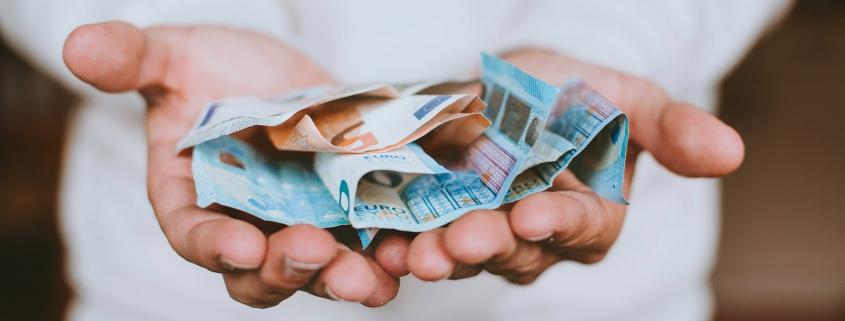 Maan houdt euro biljetten in zijn open handen.