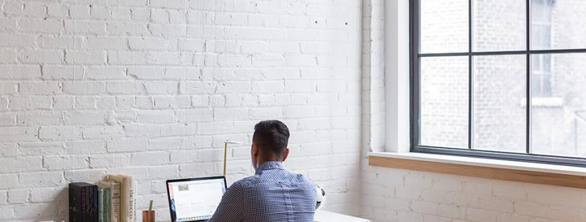 man zittend aan zijn bureau met een laptop