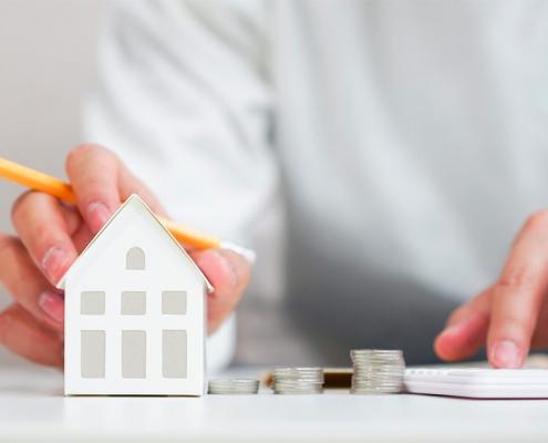 papieren huisje wat vastgehouden wordt door een hand met een potlood tussen de vingers. Andere hand is aan het rekenen op een rekenmachine